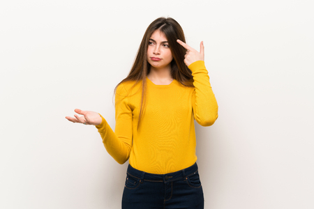 Young woman with yellow sweater making the gesture of madness putting finger on the head Reklamní fotografie