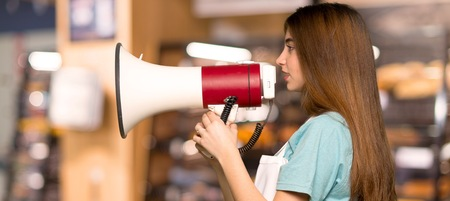 Girl with apron shouting through a megaphone in a bakery