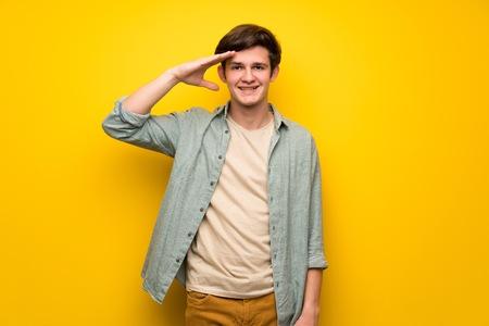 Teenager man over yellow wall saluting with hand Stock Photo
