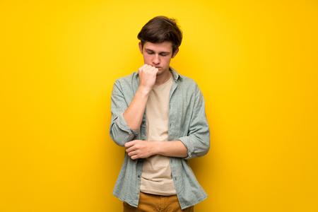 Teenager man over yellow wall having doubts Imagens - 117925023