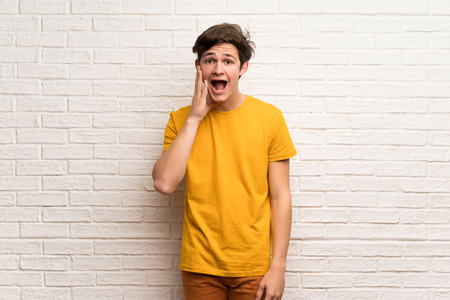 Teenager man over white brick wall with surprise and shocked facial expression 版權商用圖片
