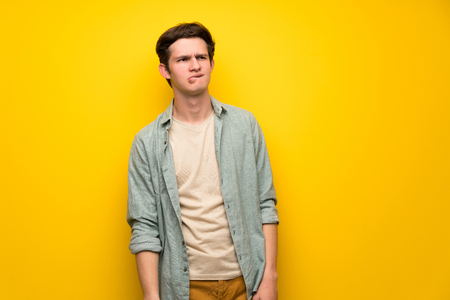 Teenager man over yellow wall with confuse face expression while bites lip Foto de archivo