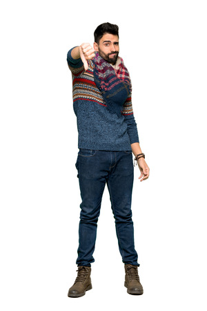 Full-length shot of Hippie man showing thumb down sign with negative expression on isolated white background