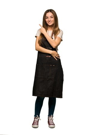 Full body Young woman with apron pointing to the side to present a product on isolated background 版權商用圖片