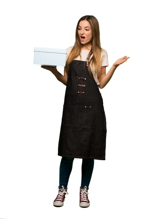 Full body Young woman with apron holding gift box in hands on isolated background