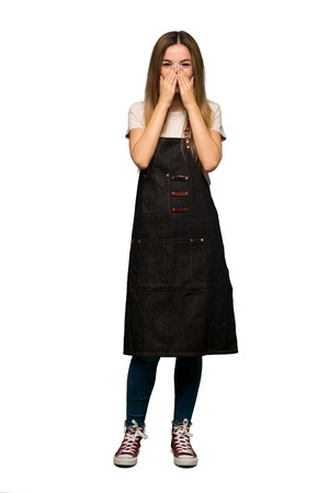 Full body Young woman with apron smiling a lot while covering mouth on isolated background
