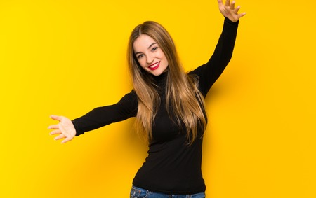 Young pretty woman over yellow background presenting and inviting to come with hand Imagens
