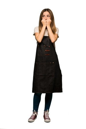Full body Young woman with apron is a little bit nervous and scared putting hands to mouth on isolated background Imagens
