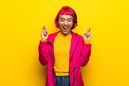 Young woman with pink hair over yellow wall with fingers crossing