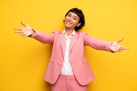 Modern woman with pink business suit presenting and inviting to come with hand