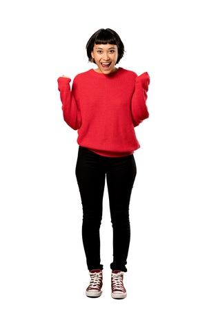Una foto de cuerpo entero de una niña de pelo corto con un suéter rojo celebrando una victoria en la posición ganadora sobre fondo blanco aislado