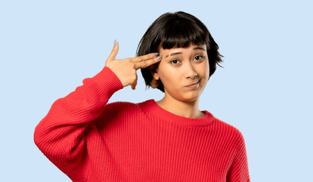 Short hair girl with red sweater with problems making gun gesture on isolated blue background Imagens