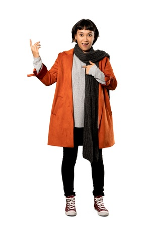 A full-length shot of a Short hair woman with coat with surprise facial expression over isolated white background Imagens