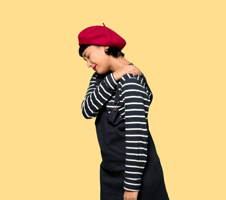 Young woman with beret suffering from pain in shoulder for having made an effort over yellow background