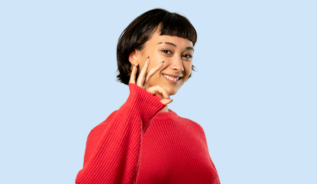 Short hair girl with red sweater showing ok sign with fingers on isolated blue background Imagens - 118457078