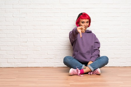 Young woman with pink hair sitting on the floor showing thumb down with negative expression