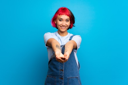 Young woman with pink hair over blue wall holding copyspace imaginary on the palm to insert an ad