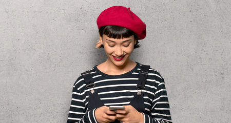 Young woman with beret sending a message with the mobile over textured wall