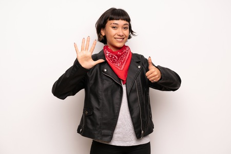 Woman with leather jacket and handkerchief counting six with fingers Stockfoto