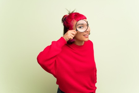 Young woman with red sweater taking a magnifying glass and looking through it Stock fotó
