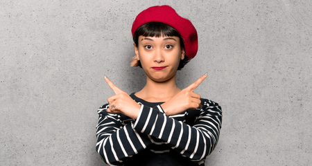 Young woman with beret pointing to the laterals having doubts over textured wall Standard-Bild