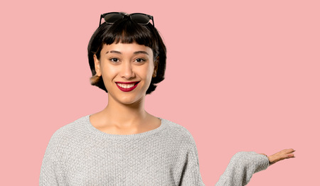 Young woman with short hair holding copyspace imaginary on the palm to insert an ad on isolated pink background