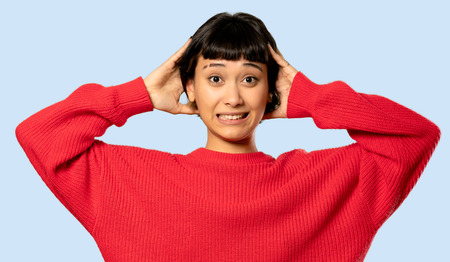 Short hair girl with red sweater frustrated and takes hands on head on isolated blue background