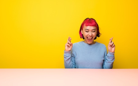 Young woman with pink hair with fingers crossing Reklamní fotografie