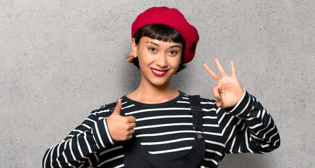 Young woman with beret showing ok sign with and giving a thumb up gesture over textured wall