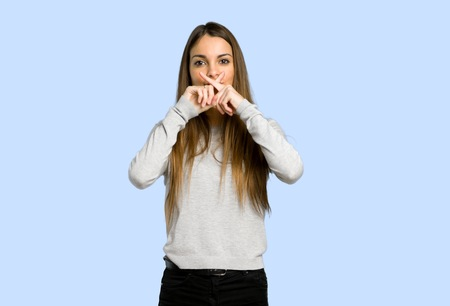 young girl showing a sign of silence gesture on blue background