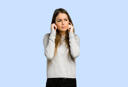 young girl covering ears with hands. Frustrated expression on blue background Stock Photo