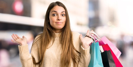 Young girl with shopping bags having doubts while raising hands and shoulders in the city Foto de archivo