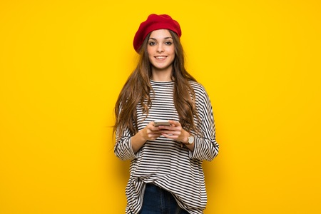Girl with french style over yellow wall sending a message with the mobile