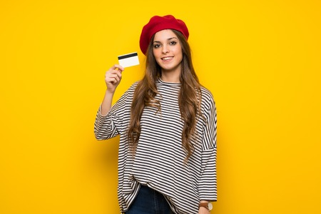 Girl with french style over yellow wall making a selfie 写真素材