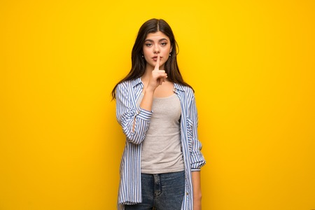 Teenager girl over yellow wall showing a sign of silence gesture putting finger in mouth