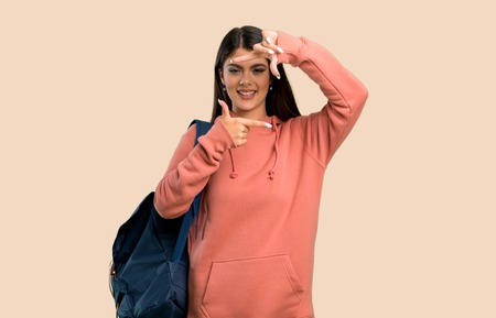 Teenager girl with sweatshirt and backpack focusing face. Framing symbol on color background