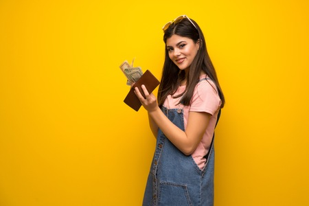 Teenager girl over yellow wall holding a wallet Фото со стока