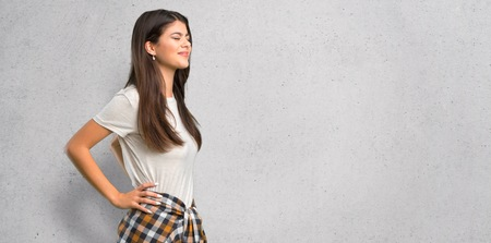 Teenager girl with shirt tied to the waist suffering from backache for having made an effort on textured wall background Stock Photo