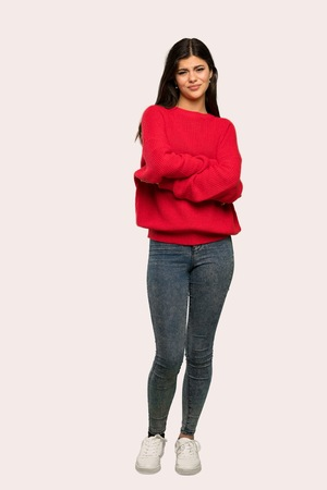 A full-length shot of a Teenager girl with red sweater feeling upset over isolated background