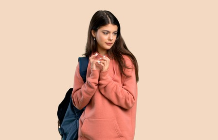 Teenager girl with sweatshirt and backpack scheming something on color background