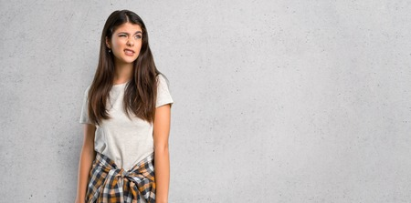 Teenager girl with shirt tied to the waist is a little bit nervous and scared pressing the teeth on textured wall background