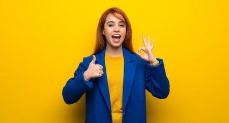 Young redhead woman with trench coat showing ok sign with and giving a thumb up gesture Imagens - 118537406