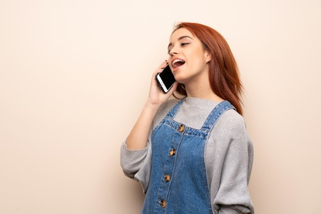 Young redhead woman over isolated background keeping a conversation with the mobile phone