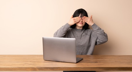 Young woman working with her laptop covering eyes by hands. Surprised to see what is ahead