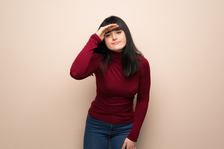 Young woman with red turtleneck looking far away with hand to look something