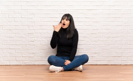 Woman sitting on the floor yawning and covering wide open mouth with hand