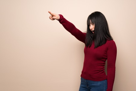 Young woman with red turtleneck pointing away