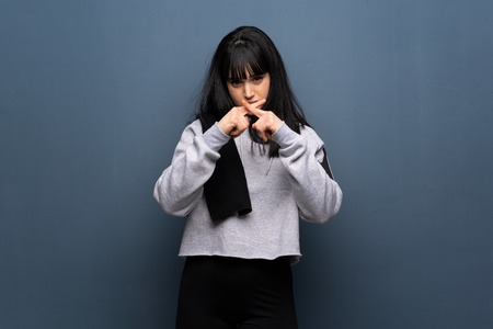 Young sport woman showing a sign of silence gesture Stock Photo