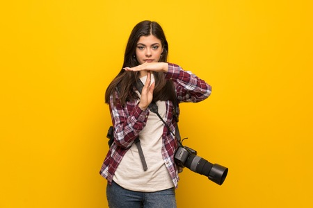 Photographer teenager girl over yellow wall making time out gesture