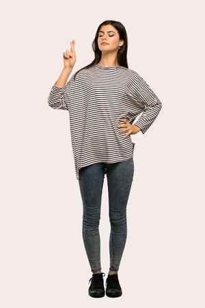A full-length shot of a Teenager girl with striped shirt with fingers crossing and wishing the best over isolated background